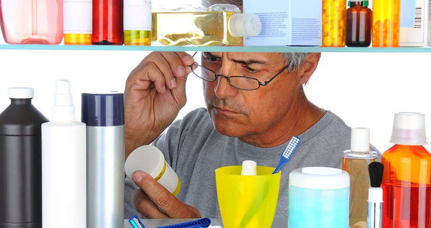 Unshaven Middle aged man reading a prescription label in front o