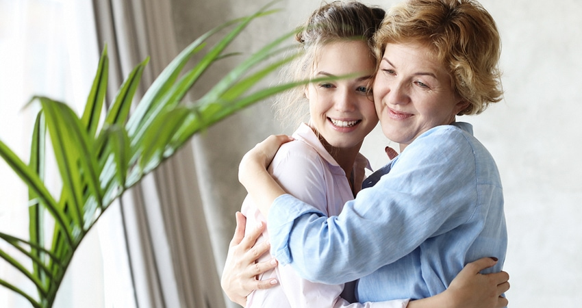 lifestyle and people concept: Happy senior mother embracing adul