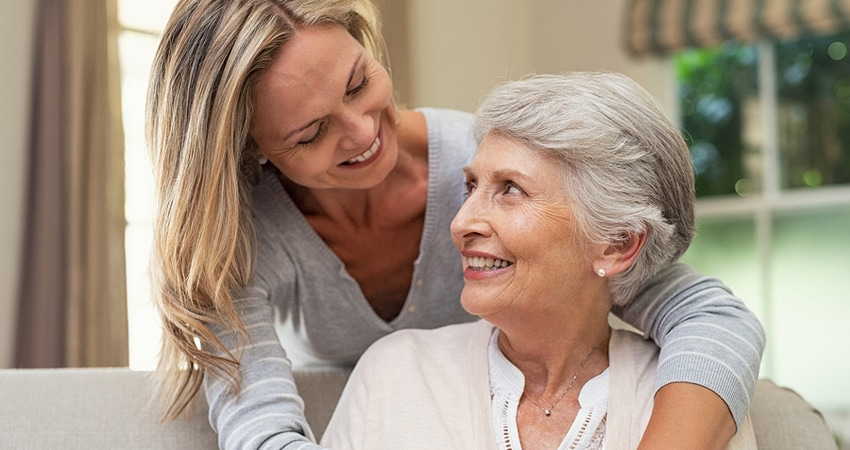 Portrait of mother and mature daughter hugging at home. Happ